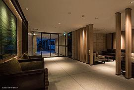 ガラスアートが印象的なエントランスホール。エントランスホールの壁はスクラッチ仕上げのライムストーンとオリジナル制作のアートで演出。また、床には御影石を配し、格調高く仕上げています。