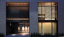 御影石の堂々たる構えが、住まいの格を印象づけます。日本の伝統的な格子デザインを採用。ブロンズ色の濃淡、縦格子のピッチの違いなどにより表情に変化をもたせました。建物前面には、格子の縦ラインと呼応するトクサを植栽しています。