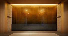 エントランスの正面に、金色に輝くアートウォールがある。日本の伝統工芸である手漉き和紙を箔ガラスで挟み、厚みをもたせることで立体感をつくり、和紙の紋様を光で浮かび上がらせている。