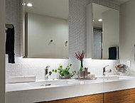 クオーツストーンのカウンターを採用した洗面化粧台。鏡の背面は、モザイクタイル貼りの化粧壁を標準仕様としました。
