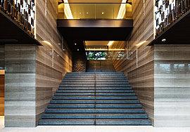 磨き抜かれた美意識と技が紡いだ二層吹き抜けのエントランスホール。中央には大地の起伏を生かした大階段が構えます。悠久の時を感じさせる天然石の趣、空間を格調高く彩る煌めきの意匠、光と緑。