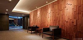 「ザ・パークハウス文京本駒込」は、不忍通りに接しながらも奥まった敷地形状。さらに敷地の高低差を活かし、少し小上がりになったエントランスアプローチには自然石を用いて存在感を語る大壁に、列柱のように植えられた高木が彩る。