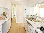 家族の気配が感じられる対面キッチン。キッチンとコーディネイトされた食器棚も装備。(21-40号地・家具付モデルハウス)