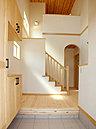 アーチ壁や装飾手すりなどで優雅な吹抜空間がひろがる開放的な玄関。