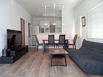 ■施工例:落ち着いた色合いの建材に、家具も併せスッキリとした住空間にまとめられたLDK。 お施主様のこだわりが凝縮された住空間となっています。