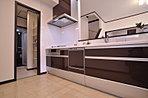 サニタリーからバスルームにつながるキッチン。巧みな空間演出で効果的にレイアウトをしています。(当社施工例)