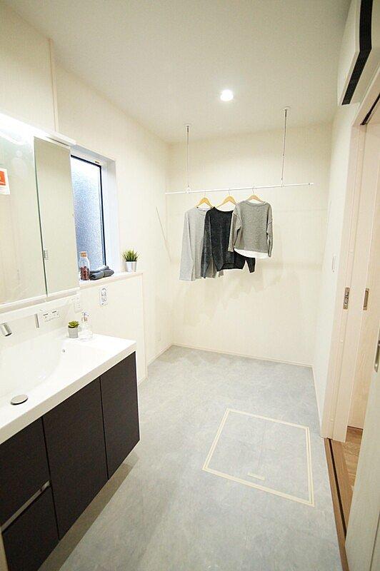 【洗面室】■洗面化粧台はスタイリッシュなLEDタイプ ■洗面室には室内物干しを設置。洗う・干すの導線がスムーズで家事ラクを実現