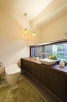 棚を大きく作り収納が多いトイレに。照明にもこだわるとお洒落♪