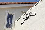 淡いトーンの外壁にオレンジの洋瓦が特徴の外観、アクセントにアイアンの飾りを施しています