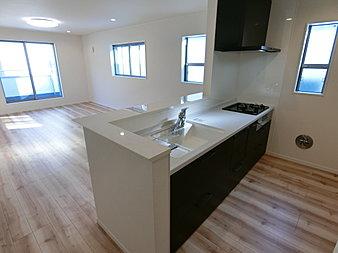 濃すぎない茶系の床材がまず印象的です。黒いキッチンの面材は高級感があります。2点で重めの色遣いをしているので、壁紙は白にしています。