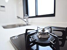 新規に交換されたシステムキッチンは、広くはないけれどもシンプルな作り。深めのシンクと三口コンロ、収納もしっかりあります。