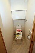 温水洗浄機能付きで清潔にご利用いただけますね。吊り戸棚もトイレ用品の収納に便利。