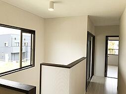 階段の窓から暖かな光の差し込む2F廊下。