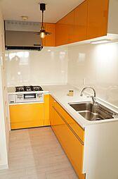 オレンジ色がアクセントのキッチン。グースネックのおしゃれな水栓