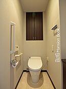 右手前側に手洗いボウルが設置されたトイレ。タンクレスでちゃんと吊戸棚もございます。