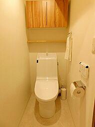 温水洗浄機能付便座トイレ。キャビネットや棚板があり、収納も充実しています