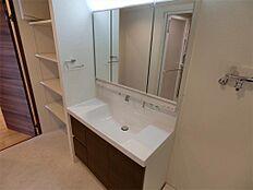 3面鏡裏収納付きの洗面化粧台です。左手にはリネン棚もあり収納豊富でゆったりとした洗面室です。