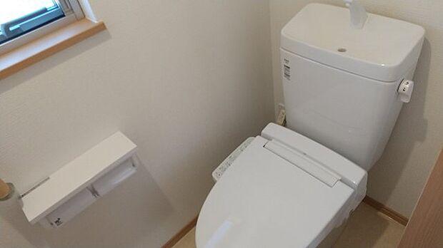 1階の白を基調とした清潔感のあるトイレ。手すりがあるので、立ち上がりもらくらく♪
