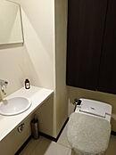 温水洗浄機能付きトイレ。手洗い器で清潔にお使いいただけます。洗面所にはドラム式全自動洗濯乾燥機を備えています。