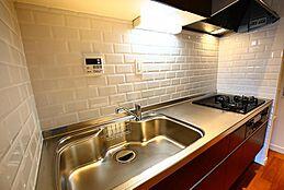 3口ガスは通常装備です。まな板を置く場所や作業するスペースも取れたキッチンの為使い勝手も宜しいかと。色は落ち着いたダークブラウンです。