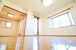 約14帖のLDK部分。光沢のあるフローリング、窓からの明るい彩光が得られており、落ち着いた居住空間の仕上がりを想わせます。