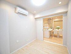 キッチン横の洋室。引き戸を開けるとLDKも広く感じます。エアコン付き。