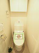 温水洗浄機能付きで、いつでも清潔にご利用いただけます。吊り戸棚付きでトイレ用品の収納にも便利ですね