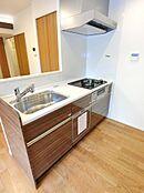 システムキッチンも交換済。木目調のフロント部分と真っ白なワークトップで、あたたかみと清潔感のある印象です。シンク部分はオープンになっており、リビングの様子をうかがいながら家事ができます。