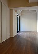こちらは洋室約6.8帖の写真です。落ち着いたカラーのフローリングとなっています。