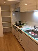 壁付けキッチンの魅力は収納力の多さです。奥には棚の高さを自由に変えられるパントリー付き。