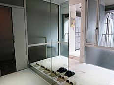 ライトコートからの採光と鏡張りでの反射が、奥行きを更に感じさせる玄関。