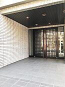 格子の扉がお洒落なエントランスです。屋根が深くまであるので、傘を指す余裕もあります。