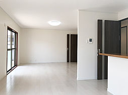 白を基調とした高級感のあるフローリングとダーク調の建具がモダンな雰囲気の明るいLDK。(3)